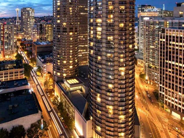 The Westin Hotel in Seattle at night with lights on in the building and cars driving by