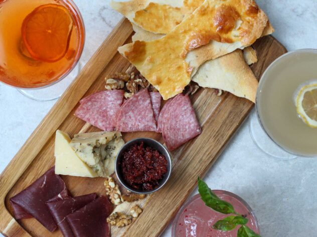 charcuterie board with different dried meats and cheese next to three different cocktails