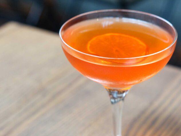 orange cocktail garnished with a slice of dried orange