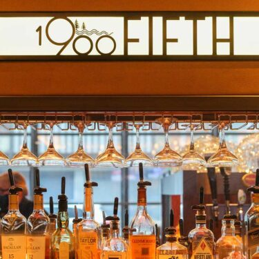 1900 Fifth Bar display of bottles of alcohol and hanging wine glasses