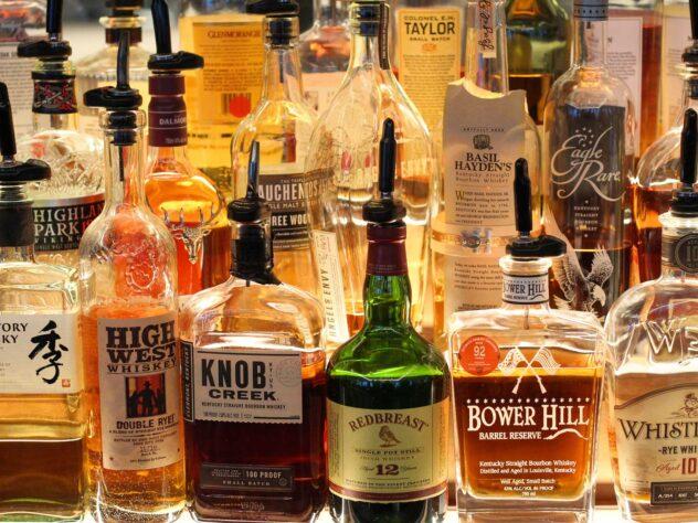 array of different liquor bottles at bar