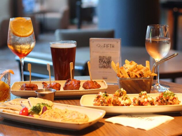 close up of appetizer small plates, cocktail, wine glass, and beer at wooden dining table