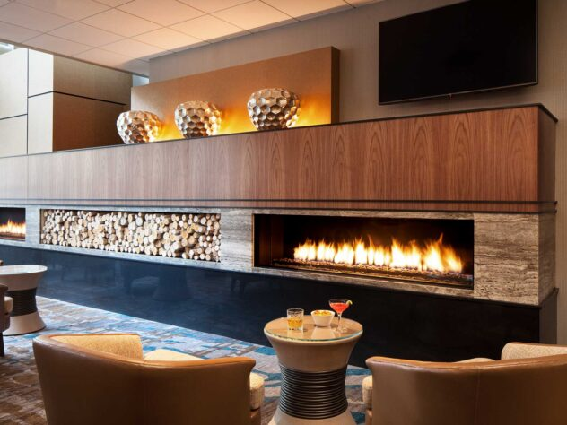 burning fireplace in slick wooden cabinet under flat screen television
