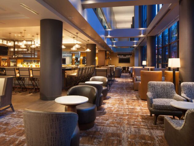 lounge area of hotel bar under dim lighting, array of seating options and large bar