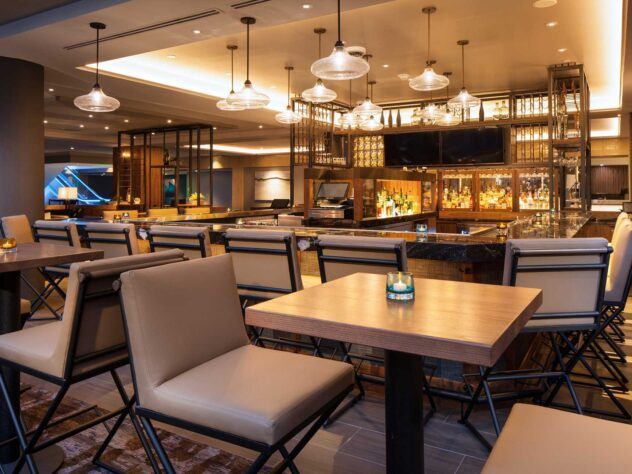 tall chairs at small square tables next to a brightly lit bar area