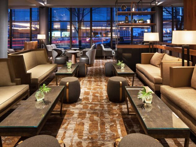 couches and tables in a large lounge with large windows with a street view