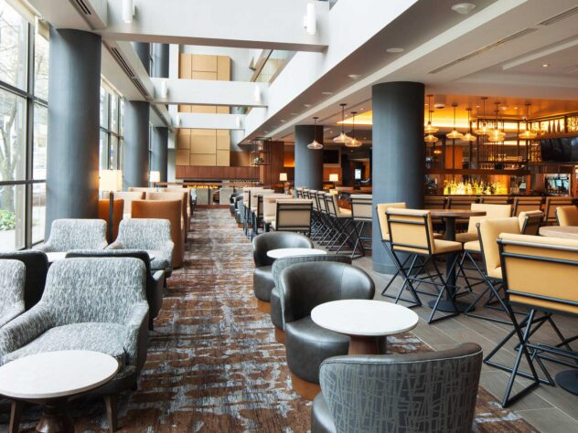 lounge seating area with a variety of couches, round tables, and large windows next to a bar