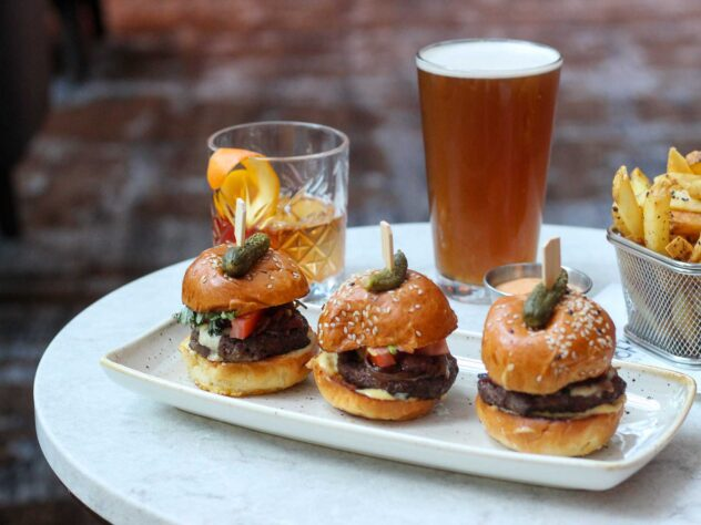 three sliders on a ceramic plate next to a cocktail, glass of beer, and basket of fries